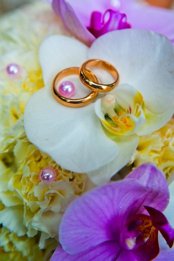 Beautiful gold jewelry lying around flowers. Wedding.Love