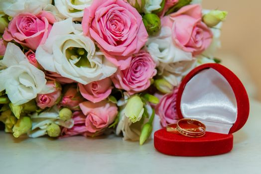 Wedding gold ring. Romantic engagement two diamond rings are in a red box in the shape of a heart, they lie near a bouquet of nevetas of pink roses and white flowers.