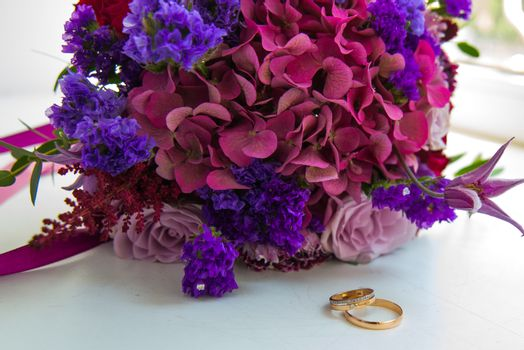 Two gold romantic wedding rings with diamonds bride and groom are next to a bouquet of lilac and violet flowers.