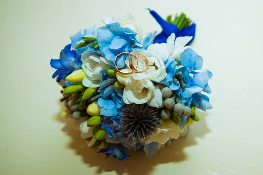 Wedding ring. Two gold romantic rings of the bride and groom are on a bouquet of blue and blue flowers.