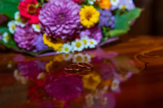 Wedding ring. Two gold rings of the bride and groom about an unusual bouquet of flowers with daisies.