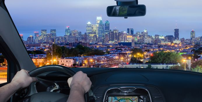 Driving a car towards Philadelphia skyline at night as seen from the Stadium District, USA