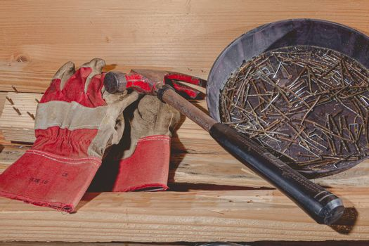 old rusty hammer and construction gloves laid on wooden board in studio