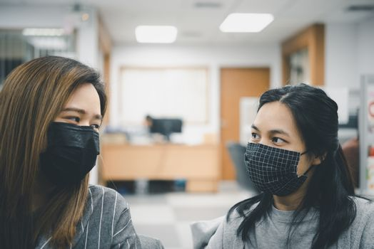 Asian pretty women wearing mask respiratory protection mask against epidemic flu covid19 or corona virus from wuhan in office with fear emotion in concept illness, outbreak, healthcare in life