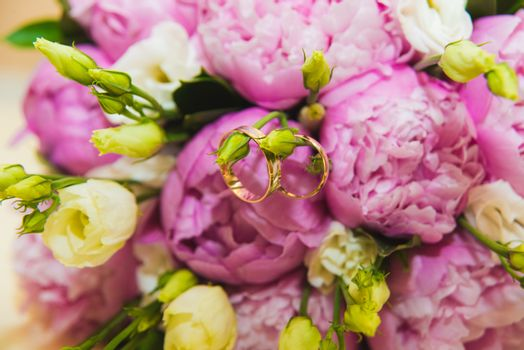 Beautiful delicate wedding bouquet of pink peonies and wedding rings of the bride and groom. Wedding day.
