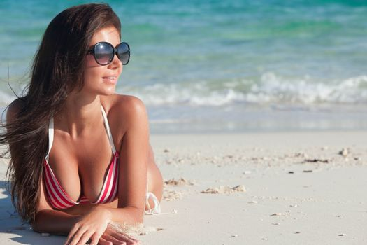 Glamorous long haired young woman in bikini and sunglasses lying on tropical beach, copy space for content