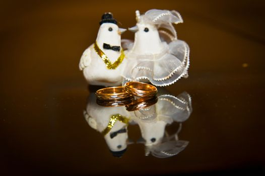 Wedding engagement gold ring, and a rag doves the bride and groom.