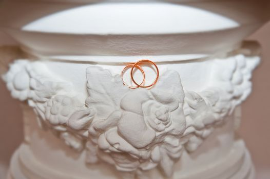 Two beautiful gold wedding rings on a background of decorative elements of the wedding day