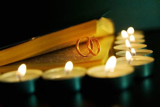 Wedding rings and candles close up. Valentine's day.