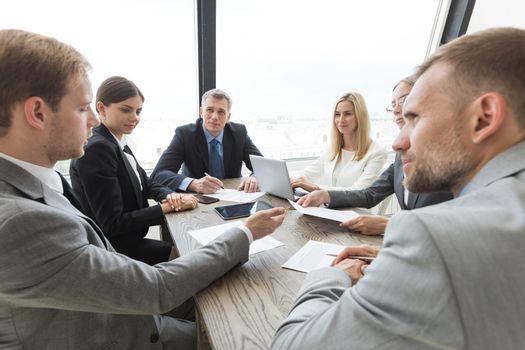Team of business people at meeting in office discuss contract terms