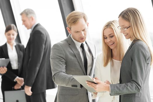 Three smart employees discussing documents using tablet pc at meeting