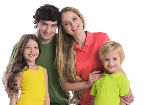 Happy young family with two children standing together embracing isolated on white background