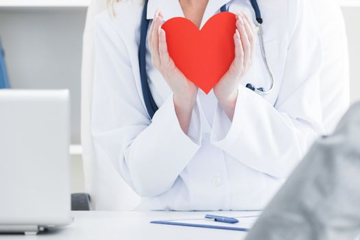 Doctor holding a red heart at hospital office, medical health care and doctor staff service concept