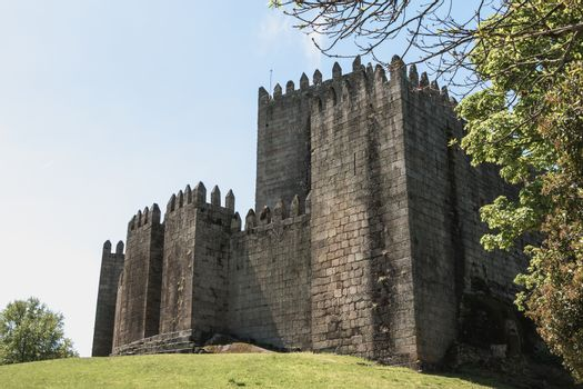 Guimaraes, Portugal - May 10, 2018: Architectural detail of the Guimaraes Castle that tourists visit on a spring day. Medieval castle inhabited by the King of Portugal Alphonse I