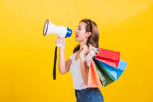 woman smiling hold shopping bags multi-color and shouting in meg