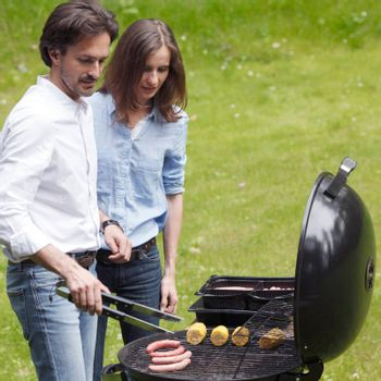 Couple cooking food corn vegetables sausage on barbecue grill at backyard