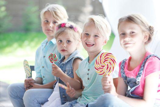 Four funny kids cute smiling friends eat enjoy lollipops outdoors