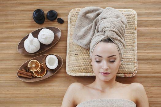Beautiful young woman relaxing in spa salon top view