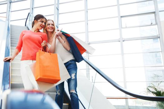 Young girls with shopping bags in shop at escalator