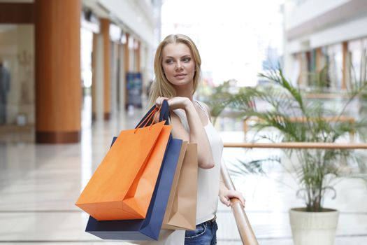 Fashion blonde shopping girl walking in mall with bags in shopping mall