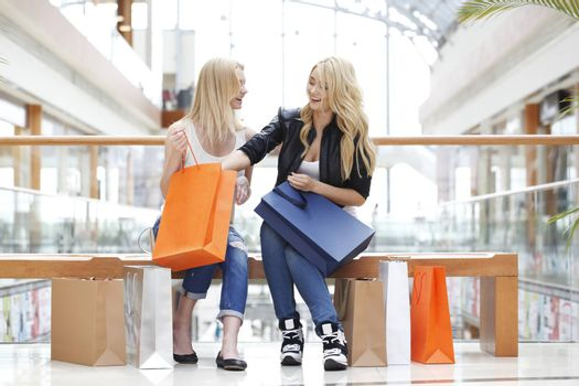 Young beautiful happy girls looking into shopping bags and laughing
