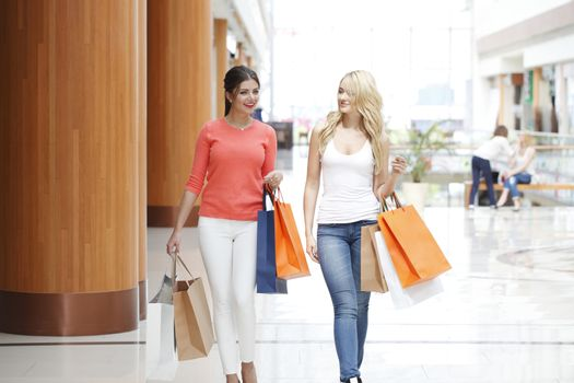 Young beautiful happy women with shopping bags walking in mall and talking