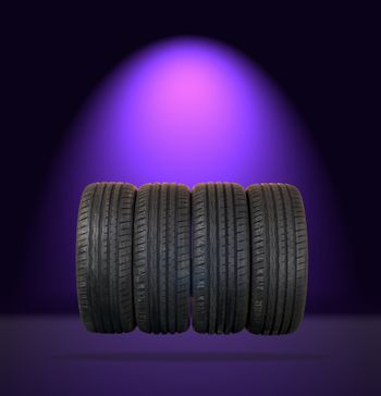 4 summer tires isolated on dark background