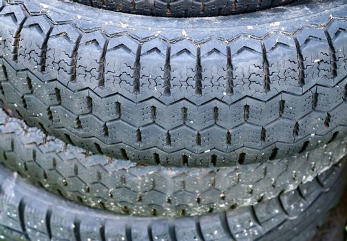 Damaged and worn old black tires on a stack. Damaged and worn ol