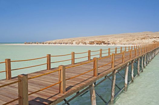 View of a tropical beach on an island with a small wooden jetty