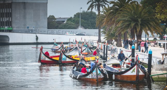 Aveiro, Portugal - May 7, 2018: Tourists walk on famous Moliceiros on a spring evening, traditional boats used to harvest seaweeds in the past