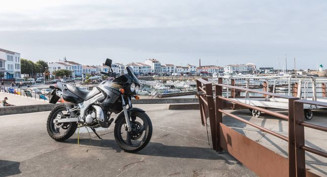 Yeu island, France - September 18, 2018: Motorcycle parked in harbor port Joinville near boats on a summer day