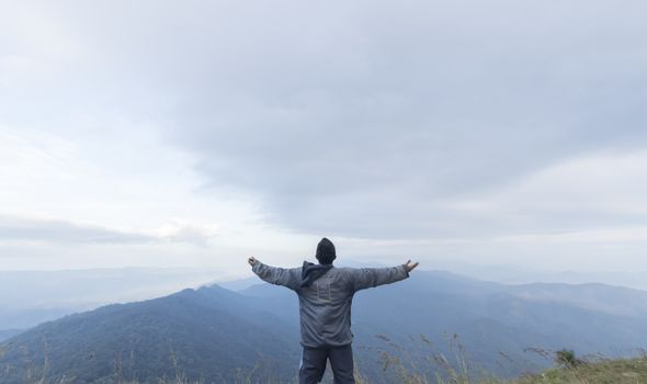 Man hand up on top of mountain,Travel concept
