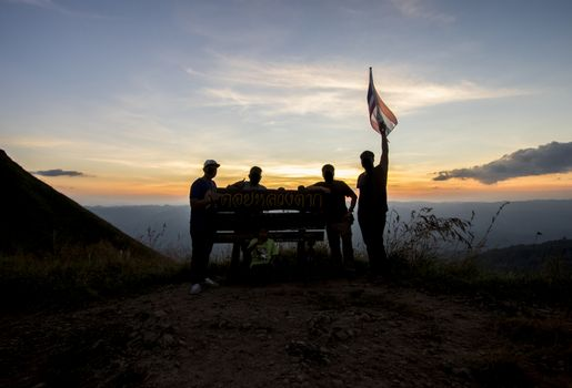 Silhouette of group of people at top of mountain at sunset