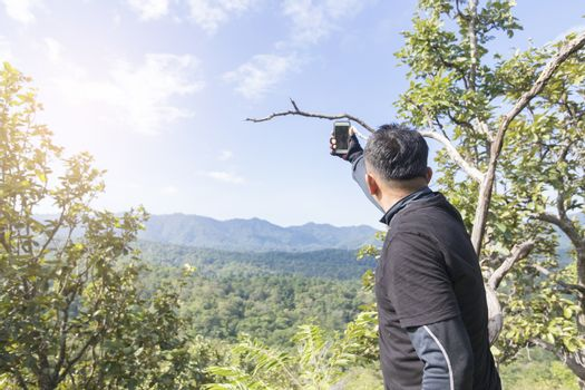 Asian man taking selfie on top of the mountain