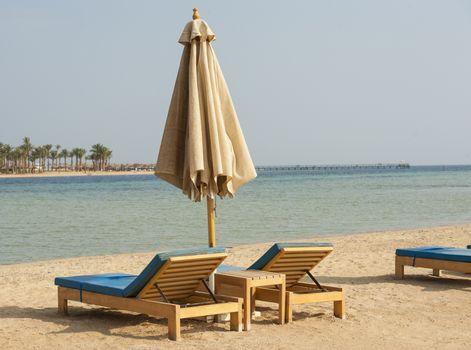 Sun loungers and a parasol on a tropical beach