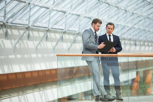 Two business people having informal meeting in modern office discussing documents
