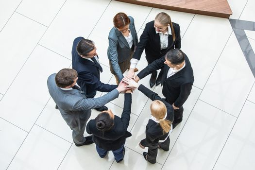 Business teamwork concept, coworkers putting hands together in a tower stacking hands unity cooperation concept, top view