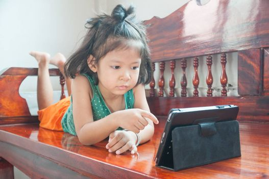 Young Girl lying on wooden stool and Learning online course on Wireless Digital Tablet while staying at home in situation of Corona Virus or Covid 19 outbreak.