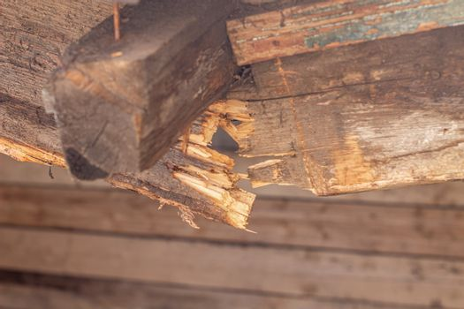 Broken wooden beam of the canopy. wooden roof of a barn destroyed due to the weather.