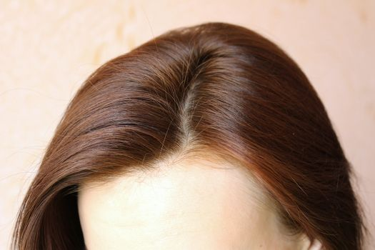 Women's hair is a top view close-up.