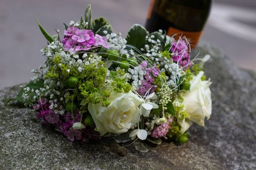 Wedding bouquet and bottle of wine.