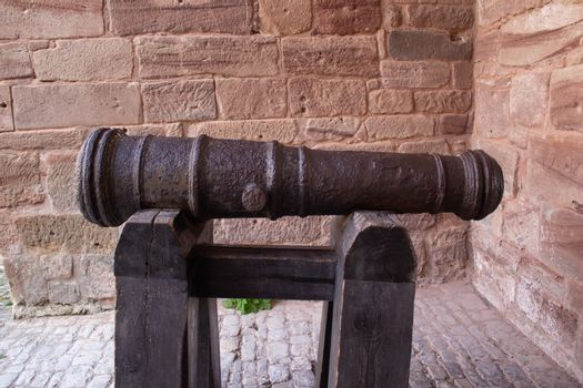 Old black cannon pointing through an opening in a castle rampart with the sea in the background