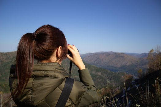 A woman looking at a beautiful landscape, the sea and the mountains through binoculars from the lookout