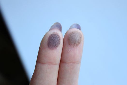 Swatches of shimmer palette eyeshadows on a woman's fingers. Wood background