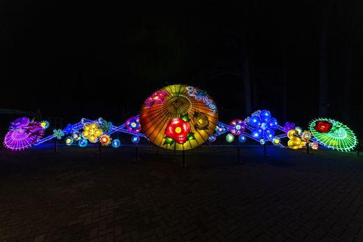 Illuminated umbrella forming a illuminated corridor or pathway in the dark night