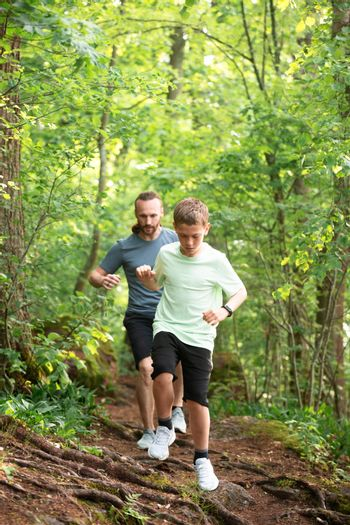 Father and son run in forest