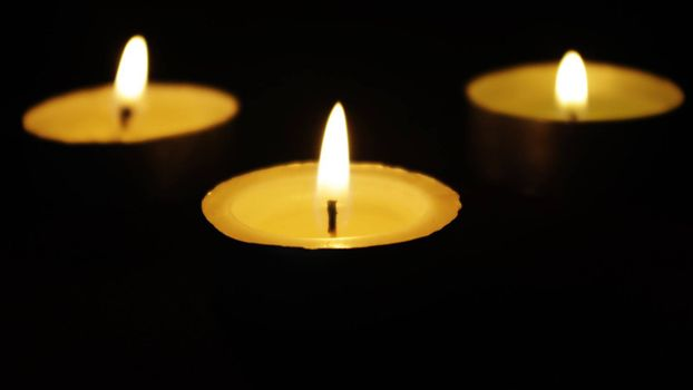three memorial candles in darkness