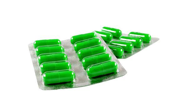 green antibiotic pills on white background