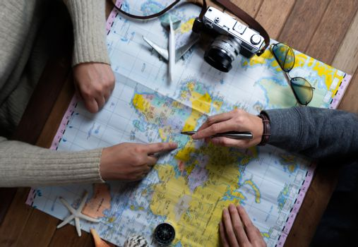 Friend planning for vacation trip with accessories of traveler