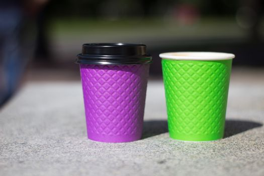 purple and green paper coffee Cup on the stove